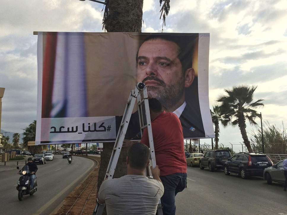 Lebanese workers post signs decrying the Saudi kidnapping of popular prime minister Saad Hariri