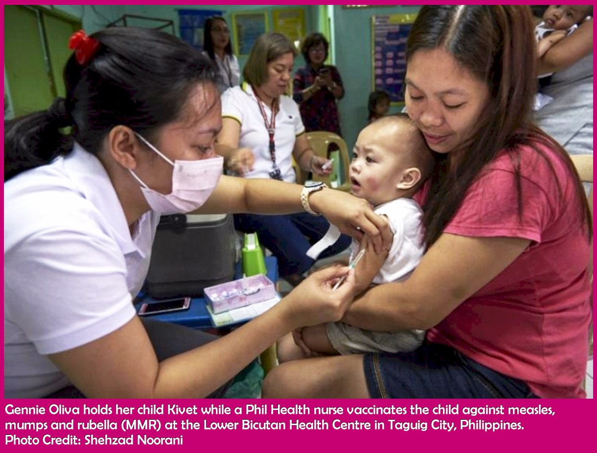 Gennie Oliva holds her child Kivet while a Phil Health nurse vaccinates the child against measles, mumps and rubella (MMR) at the Lower Bicutan Health Centre in Taguig City, Philippines. Photo Credit: Shehzad Noorani
