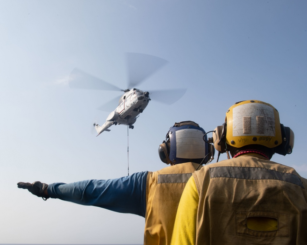 (Sept. 12, 2019) Aviation Boatswain's Mate (Handling) 1st Class Joseph Martinez, assigned to amphibious assault ship USS Boxer (LHD 4), signals a Military Sealift Command SA-330J Puma helicopter with Aviation Boatswain's Mate (Handling) Airman Johnny Snowden, also assigned to Boxer, on the flight deck during a vertical replenishment-at-sea. Boxer is part of the Boxer Amphibious Ready Group and 11th Marine Expeditionary Unit and is deployed to the U.S. 5th Fleet area of operations in support of naval operations to ensure maritime stability and security in the Central Region, connecting the Mediterranean and the Pacific through the Western Indian Ocean and three strategic choke points. (U.S. Navy photo by Mass Communication Specialist 2nd Class Dale M. Hopkins/Released)